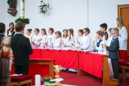 NANDLSTADT, ALLEMAGNE - 7 MAI 2017: Un groupe de jeunes filles et garçons debout alignés à l'église et tenant des bougies allumées lors de leur première communion à Nandlstadt, en Allemagne.