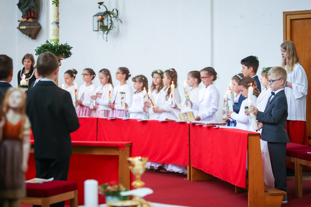 NANDLSTADT, GERMANY - MAY 7, 2017 : A group of young girls and boys standing lined up in church and holding lighted candles at their first communion in Nandlstadt, Germany.