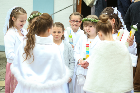NANDLSTADT, GERMANY - MAY 7, 2017 : A group of young girls holding candles and standing in front of church at their first communion in Nandlstadt, Germany.