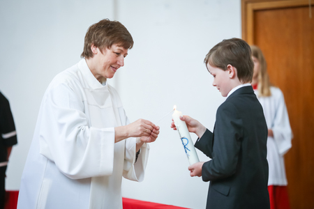NANDLSTADT, GERMANY - MAY 7, 2017 : The priests assistant helping a boy to light up the candle in church at the first communion in Nandlstadt, Germany.