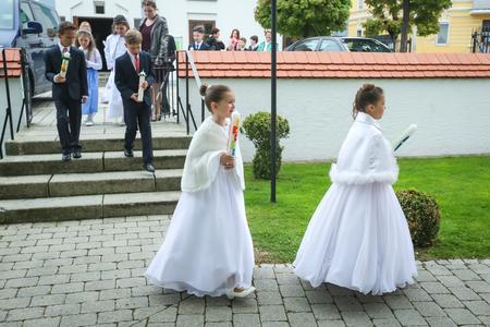 NANDLSTADT, ALLEMAGNE - 7 MAI 2017: jeunes filles et garçons tenant des bougies et se dirigent vers l'église lors de leur première communion à Nandlstadt, en Allemagne. Éditoriale