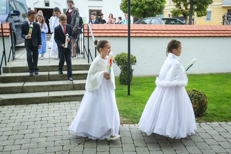 NANDLSTADT, GERMANY - MAY 7, 2017 : Young girls and boys holding candles and heading for the church at their first communion in Nandlstadt, Germany.