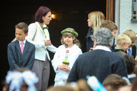 NANDLSTADT, ALLEMAGNE - 7 MAI 2017: Une jeune fille avec des bougies et des adultes debout devant l'église lors de la première communion à Nandlstadt, en Allemagne.