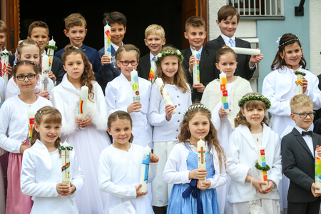 NANDLSTADT, GERMANY - MAY 7, 2017 : A group of young girls and boys holding candles lined up and posing for photographing at their first communion in Nandlstadt, Germany.