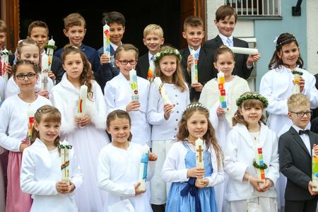 NANDLSTADT, ALLEMAGNE - 7 MAI 2017: Un groupe de jeunes filles et garçons tenant des bougies alignées et posant pour la photographie lors de leur première communion à Nandlstadt, en Allemagne. Éditoriale