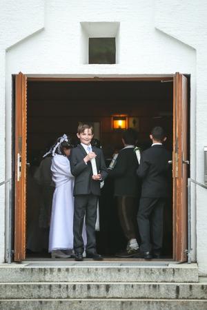 NANDLSTADT, ALLEMAGNE - 7 MAI 2017: Un jeune garçon en costume tenant une bougie et regardant la caméra à l'entrée d'un édifice d'église avec d'autres communicants derrière lui lors de la première communion à Nandlstadt, en Allemagne.