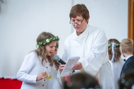 NANDLSTADT, GERMANY - MAY 7, 2017 : A young girl reading communion verses from the paper held by the priests assistant at the first communion in Nandlstadt, Germany. Éditoriale