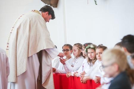 NANDLSTADT, ALLEMAGNE - 7 MAI 2017: Le prêtre donne aux jeunes garçons et filles le pain sacramentel lors de leur première communion à Nandlstadt, en Allemagne.