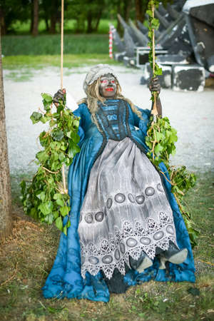 LUKAVEC, CROATIA - MAY 27, 2017 : Woman dressed as witch sitting on a swing on the Perunfest, festival of forgotten tales and folk tales held at Lukavec Castle in Lukavac, Croatia.