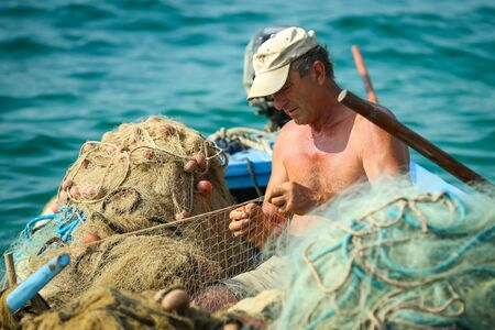 NJIVICE, CROATIA - JUNE 24, 2017 : A fisherman in an anchored boat checking the fishing net in Njivice, Croatia. Editorial