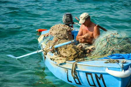 NJIVICE, CROATIA - JUNE 24, 2017 : A fisherman in an anchored boat checking the fishing net in Njivice, Croatia. Editorial