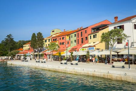 NJIVICE, CROATIA - JUNE 24, 2017 : People on the seafront with colorful architecture of hotel Jadran in Njivice, Croatia. Editorial