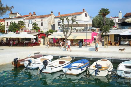 seafronts: NJIVICE, CROATIA - JUNE 24, 2017 : Anchored boats lined up with people at the seafront full of restaurants in Njivice, Croatia.