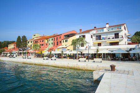 NJIVICE, CROATIA - JUNE 24, 2017 : People on the seafront with colorful architecture of hotel Jadran in Njivice, Croatia. Editorial