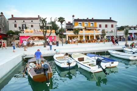 NJIVICE, CROATIA - JUNE 24, 2017 : Anchored boats lined up with people at the seafront full of shops and restaurants at sunset in Njivice, island of Krk, Croatia. Editorial