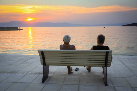 Two senior women enjoying the sunset on the bench at the waterfront in Njivice,  island Krk, Croatia.