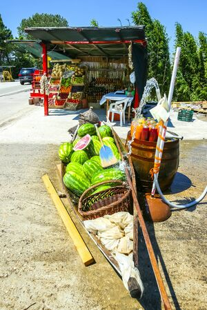 Watermelons in a boat and fresh homemade fruit juices on a barrel displayed at a food stand next to the river Neretva in Croatia.