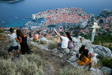 srd: DUBROVNIK, CROATIA - JULY 20, 2017 : Tourists on Srd mountain taking photos of the ancient old town in Dubrovnik, Croatia. Editorial