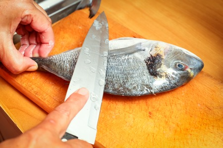 gutted: Detail of preparing bream fish on chopping board. Stock Photo