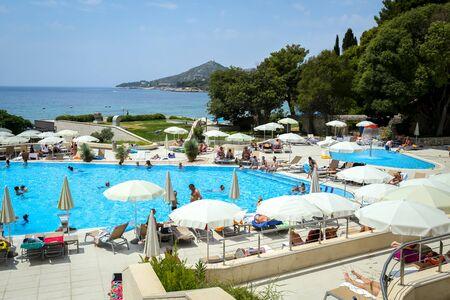 MLINI, KROATIË - JULI 22, 2017: Mensen die en bij de pool bij Hotel Astarea in Mlini, Kroatië baden zonnebaden. Redactioneel
