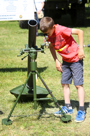 ZAGREB, CROATIA - MAY 28, 2017 : A boy sightseeing mortar 120 mm M 75 at the 26th anniversary of the formation of the Croatian Armed Forces on Lake Jarun in Zagreb, Croatia.