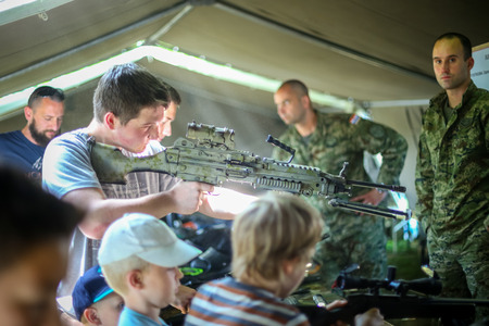 ZAGREB, CROATIA - MAY 28, 2017 : A boy checking the M249 SAW machine gun on the 26th anniversary of the formation of the Croatian Armed Forces on Lake Jarun in Zagreb, Croatia.