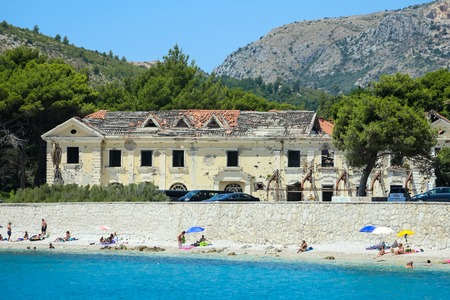 KUPARI, CROATIA - JULY 18, 2017 : People swimming and sunbathing on a sea beach next to an old building of hotel Grand Kupari in Kupari, Croatia.