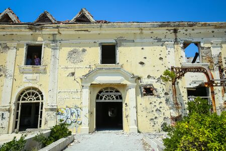 KUPARI, CROATIA - JULY 19, 2017 : People sightseeing the old ruined hotel Grand in abandoned Yugoslavian military resort in Kupari, Croatia.
