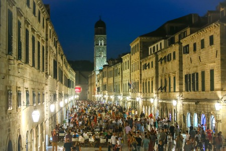 DUBROVNIK, CROATIA - JULY 22, 2017 : People walking in the main city street Stradun with the bell tower of the Franciscan church and monastery in the background in Dubrovnik, Croatia.