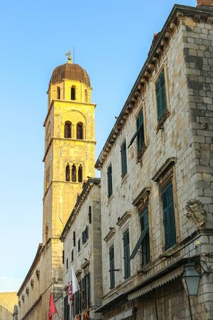 The bell tower of the Franciscan church and monastery in the main city street Stradun in Dubrovnik, Croatia. Stock Photo
