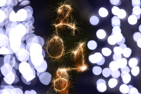 Isolated 2018 sign written with sparkle firework on black background with blurred decoration lights, happy new year 2018 concept.