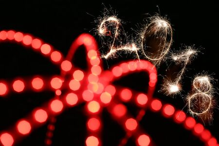 2018 sign written with sparkle firework on black background with blurred red lines, happy new year 2018 concept.
