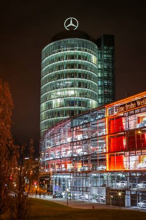MUNICH, GERMANY - DECEMBER 11, 2017 : A view of the Mercedes Benz dealership office building exterior with cars exhibited in the shop windows at night in Munich, Germany.