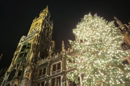 MUNICH, GERMANY - DECEMBER 11, 2017 : A low angle view of the decorated illuminated Christmas tree and the New Town Hall on Marienplatz at night in Munich, Germany.