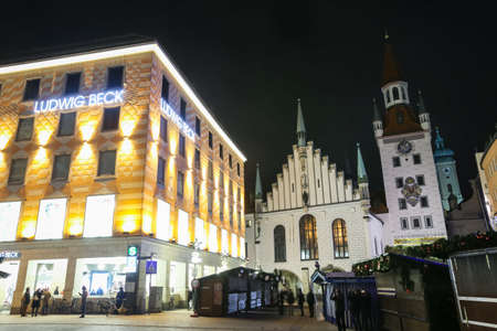 MUNICH, GERMANY - DECEMBER 11, 2017 : People on Marienplatz at Advent time with the illuminated Ludwig Beck department store and Old Town Hall at night in Munich, Germany. Editorial