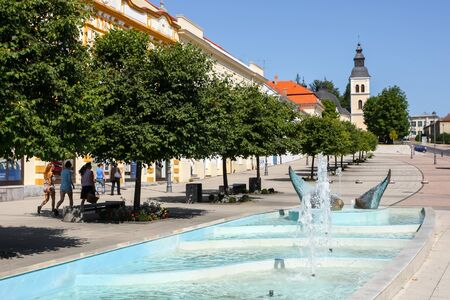 DARUVAR, CROATIA - AUGUST 16, 2013 : People are walking beside the water fountain with Church of the Holy Trinity in the background in the center of Daruvar, Croatia.