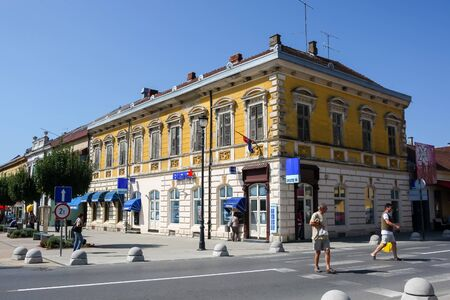 DARUVAR, CROATIA - AUGUST 16, 2013 : Old style architecture with Erste bank and people crossing the main street in the center of Daruvar, Croatia.