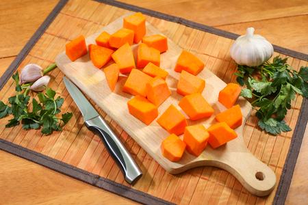 Raw pumpkin chopped on the cutting board, prepared for making pumpkin soup.