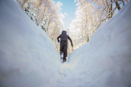 Low angle view of hiker walking on the path with fresh deep snow in the forest on the hill.