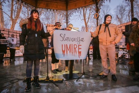 ZAGREB, CROATIA - 3rd MARCH, 2018 : Protesters hold sign Slavonija is dying on protest against the financial enforcement law that is terrorizing financially blocked people, in Zrinjevac Park, Zagreb, Croatia.