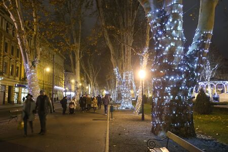 ZAGREB, CROATIA - DECEMBER 13th, 2017: Advent time in city center of Zagreb, Croatia. People passing through the Zrinjevac park ornate with illuminating trees.