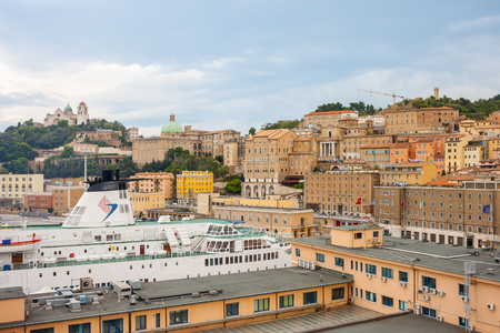 ANCONA, ITALY - 10 JULY, 2011: Cityscape of Ancona with ferries at the port viewed from the sea and cathedral of Saint Cyriacus in the background.