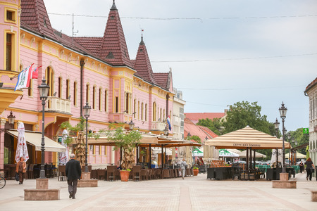 VINKOVCI, CROATIA - MAY 14, 2018 : People walking by the  empty coffee bar terrace in the King Zvonimir street in city center of Vinkovci, Croatia. Editorial