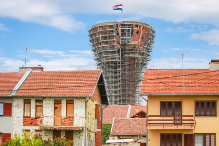 VUKOVAR, CROATIA - MAY 14, 2018 : A view of a house damaged in war with the Vukovar water tower in the background.The water tower is a symbol of the city suffering in the Croatian War of Independence.