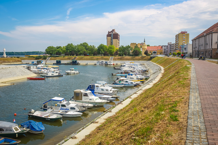 VUKOVAR, CROATIA - MAY 14, 2018 : A view of boats moored on the coast of the river Dunav with people walking on the promenade and the Hotel Dunav in the background in Vukovar, Croatia. Editorial