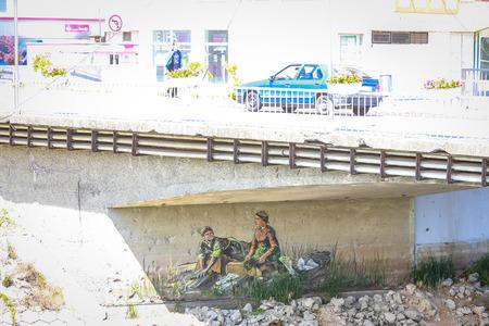 VUKOVAR, CROATIA - MAY 14, 2018 : A mural of women washing laundry on the wall under the bridge across river Vuka in Vukovar, Croatia. Editorial