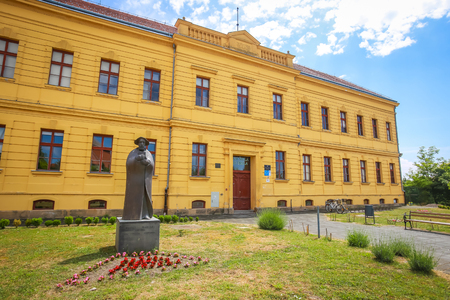 VUKOVAR, CROATIA - MAY 14, 2018 : Exterior of Gymnasium Vukovar building with statue of Marko Marulic set up in front of the building.