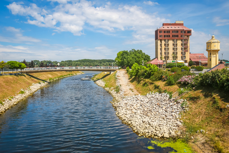 VUKOVAR, CROATIA - MAY 14, 2018 : View of the pedestrian bridge across river Vuka with abandoned hotel Dunav in Vukovar, Croatia. Editorial