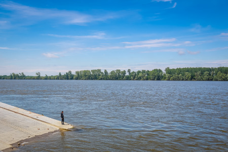 VUKOVAR, CROATIA - MAY 14, 2018 : Man standing on a new embankment on the shore of river Danube in Vukovar, Croatia. Danube is Europes second longest river. Editorial