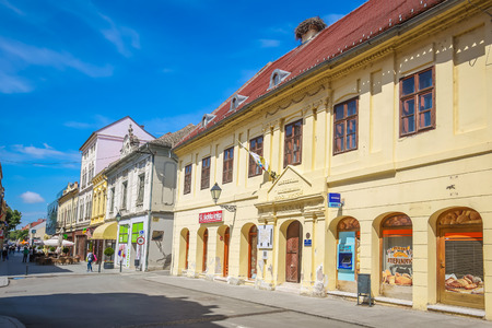 VUKOVAR, CROATIA - MAY 14, 2018 : Renovated buildings from destruction of the Yugoslav war in 90s with people walking down the street in the center of Vukovar, Croatia.